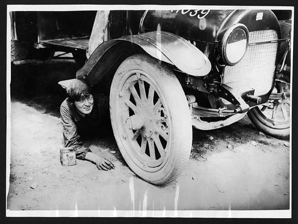 (276) C.1951 - One of the lady ambulance drivers underneath her car attending to something that has gone wrong